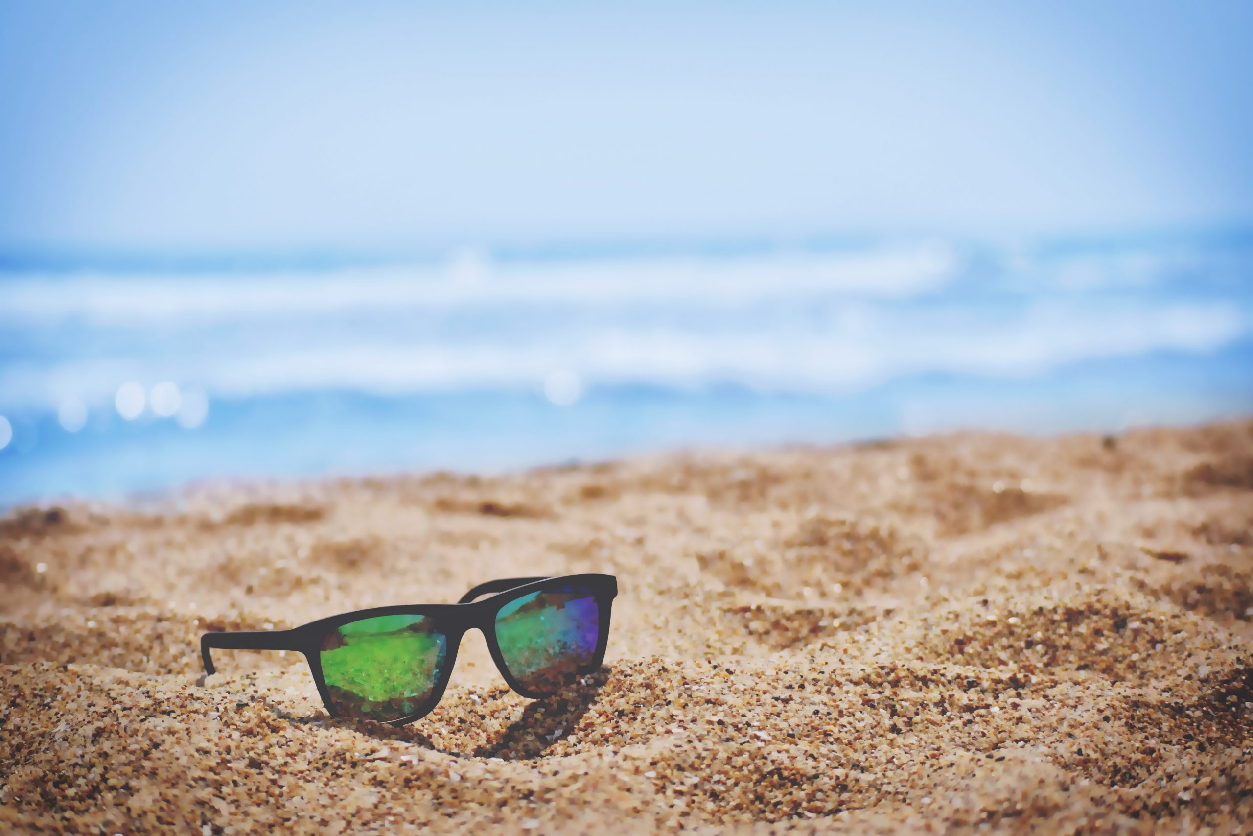pair of sunglasses on beach